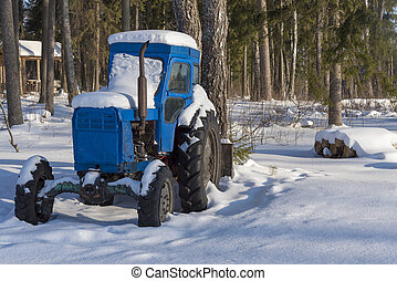 Snow-covered tractor in the woods near the village.