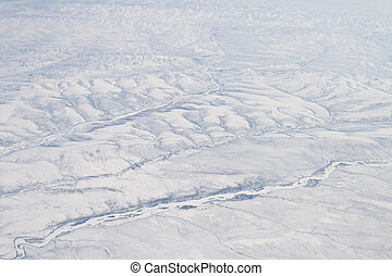 Snow Covered Verkhoyansk Mountains from airplane northern Siberia, Sakha Republic, Russia. River in foreground may be Olenyok River