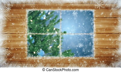 Snow-covered window with Christmas tree and falling...