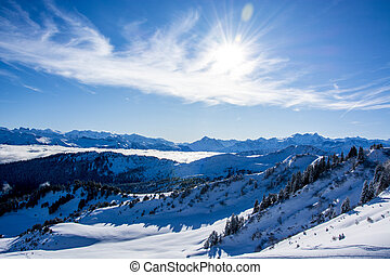 snow covered winter mountain panorama on a sunny day, blue sky