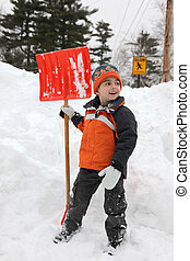 Adorable five year old boy shoveling snow.