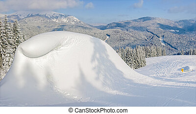 Snow-drift beside of ski piste on background of mountain