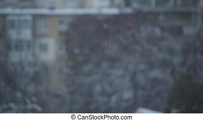 Snow falling in city on blurred background of a building