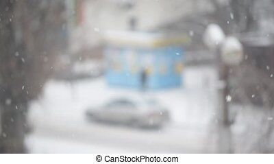 Snow falling on blurred background in city