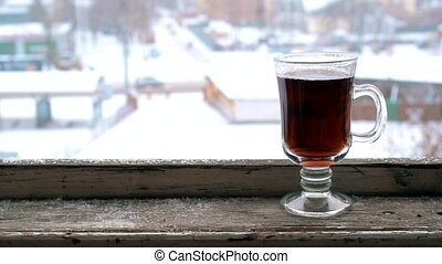 Snow falling on glass cup on old wooden window sill - Snow...