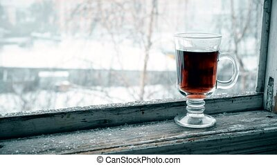 Snow falling on glass cup with tea on window sill