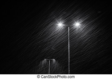 Snow falling on the background of a burning street lamp.