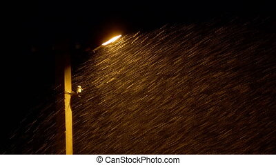 Snow Falls Against the Background of a Lamppost at Night