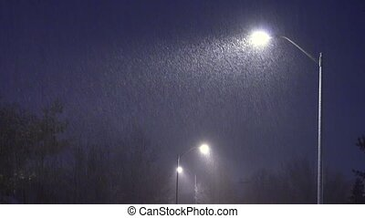 Snow falls against the background of lamppost at night. Night winter street lamp with falling snow.