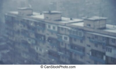 Snow falls behind the window with blurred background of the neighborhood blocks