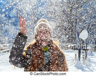 Snow falls from above on a joyful girl illuminated by the sun