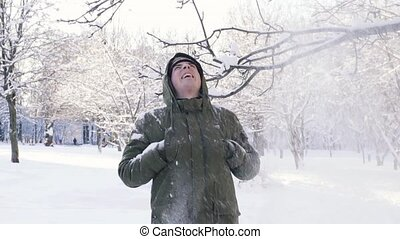 Snow falls from the branch. A man covers his head with a hood. Slow motion.