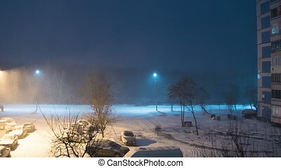 Snow Falls in the Street Against the Background of a Lamppost at Night. Time Lapse