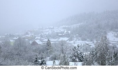 Snow falls on small village at foot of wooded hill, low...