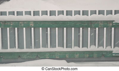 Snow falls on the background of small fence