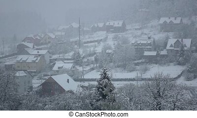 Snow falls on village at foot wooded hill. Slow motion -...