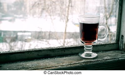 Snow falls with glass cup of tea on window sill