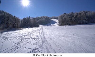 Snow forest and skiers on a ski lift pov, sunny day