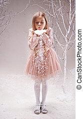 Snow fun - Cute little girl in smart dress blowing...