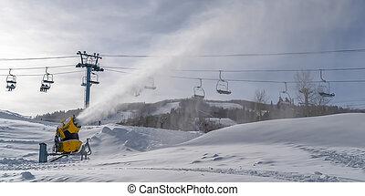 Snow gun against ski lifts and cloudy sky in Utah. Snow gun...