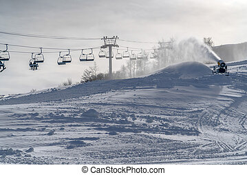Snow gun and ski lifts on a sunny winter in Utah