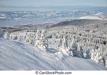 Snow gun on the ski slope and winter mountain landscape