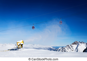 snow gun working against blue sunny sky at ski resort