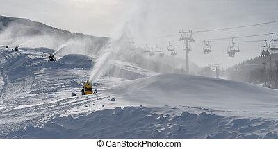 Snow guns and ski lifts on snow covered mountain. Snow guns...