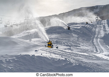 Snow guns and ski lifts on snowy slope - Snow guns and ski...