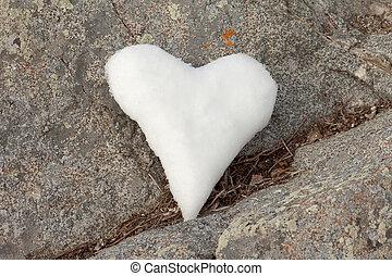 Snow heart on rock
