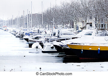 Snow in the city - yachts in winter harbor