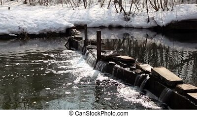Snow lay on coast of river with small waterfall on dam
