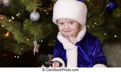 Snow Maiden - Girl in Christmas clothes near Christmas tree...