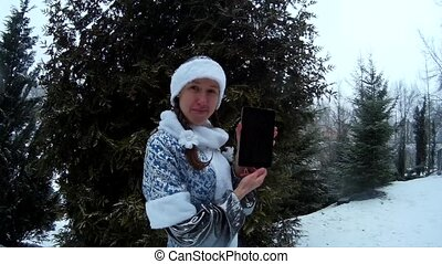 Snow Maiden in forest shows tablet computer in front of firm pine tree smiling