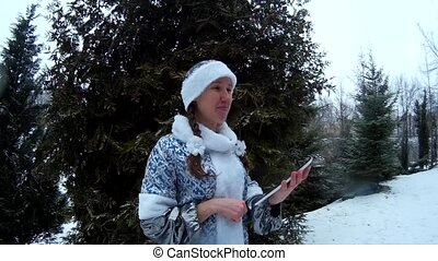 Snow Maiden in forest with tablet computer in front of firm...