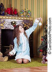 Snow-maiden looking at Christmas balls