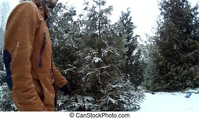 Snow Maiden snegurochka in forest presents gift to a man in front of pine tree Ukraine