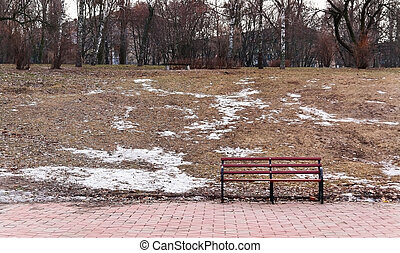snow melts in the city park with a bench