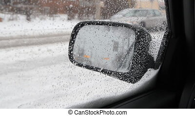 Snow mirror. - View of traffic in side mirror on a wet and...