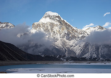 Thonak Tsho lake and Kanchung mountain with clouds passing above Ngozumpa glacier. Everest region, Himalayas, Nepal.