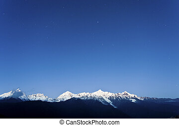 Snow mountain at dawn with stars