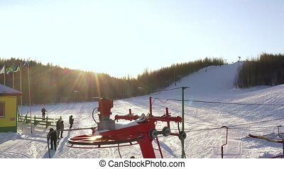 Snow mountain glade with ski lifts. Skiers and snowboarders climb the mountain using a ski lift
