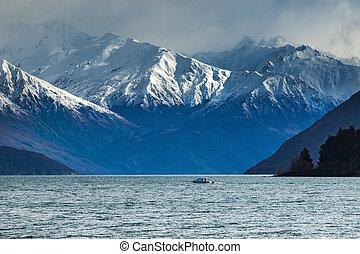snow mountain scene and motor boat over lake wanaka...