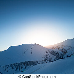 Snow mountains against the sun. Winter background