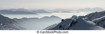 Snow Mountains Panorama in low lying inversion valley fog. Silhouettes of foggy Mountains. Scenic snowy winter landscape. View from Stuiben to Saentis. Alps, Allgau, Bavaria, Germany.