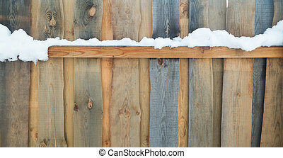 snow on a wooden fence