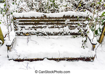 Snow On Bench Swing - Snow covers a bench swing.