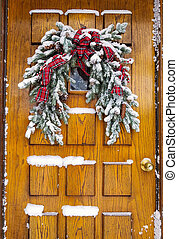 snow on Christmas pine bough on door