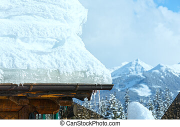 Snow on roof and winter mountain behind. - Snow on roof and...