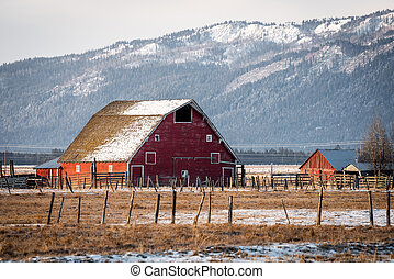Snow on the roof of an old red barn